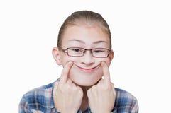A menina mostra um sorriso artificial, fotografia de stock