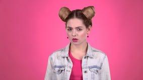 A menina mostra uma emoção diferente Fundo cor-de-rosa video estoque