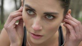 A menina motivado nova está vestindo fones de ouvido e corredor no parque no verão, estilo de vida saudável, concepção do esporte video estoque
