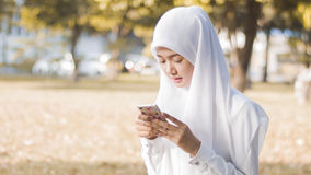 Menina muçulmana asiática nova que usa o telefone celular Fotografia de Stock