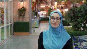 Menina muçulmana atrativa que sorri olhando a câmera filme
