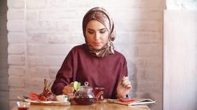 Menina muçulmana bonita no hijab no café filme