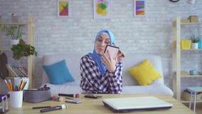 A menina muçulmana bonita no hijab faz a composição, retrato video estoque