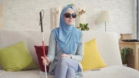 Menina muçulmana cega bonita com um bastão no hijab que vai para uma caminhada filme