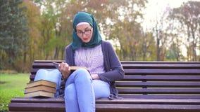 Menina muçulmana do estudante bonito no hijab que lê um livro em um banco no por do sol filme