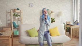 Menina muçulmana expressivo alegre no hijab no microfone do karaoke em casa filme