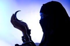 Menina muçulmana nova bonita que guarda um símbolo da lua, espiritualidade, foto de stock