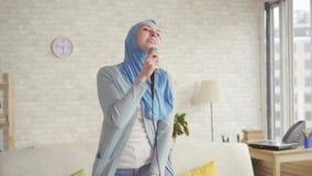 Menina mu?ulmana expressivo alegre no hijab no microfone do karaoke em casa vídeos de arquivo