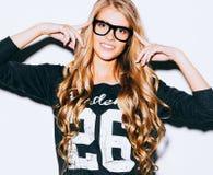 Menina muito bonita com cabelo louro longo que aponta o dedo em seus vidros elegantes Fim acima indoor Cor morna imagens de stock