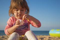A menina muito bonita que come franceses frita e molho menina que senta-se na areia na praia contra o mar Imagens de Stock Royalty Free