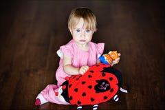Menina muito bonito que senta-se no assoalho e que guarda um rapaz do brinquedo Fotografia de Stock Royalty Free