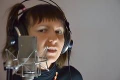 A menina, mulher em um estúdio de gravação canta uma música Fotografia de Stock