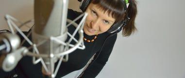 A menina, mulher em um estúdio de gravação canta uma música Imagem de Stock Royalty Free