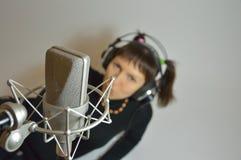 A menina, mulher em um estúdio de gravação canta uma música Fotos de Stock