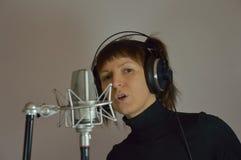 A menina, mulher em um estúdio de gravação canta uma música Fotos de Stock Royalty Free