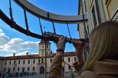 A menina, a mulher olha em um telescópio antigo velho na construção medieval europeia do turista, o castelo, o palácio fotos de stock