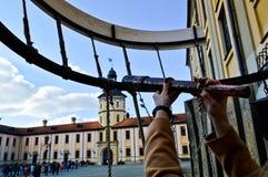 A menina, a mulher olha em um telescópio antigo velho na construção medieval europeia do turista, o castelo, o palácio fotografia de stock