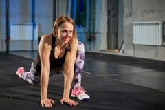 Menina muscular bonita nas caneleiras cinzentas que fazem o esticão Ostenta o gym no estilo industrial Imagem de Stock
