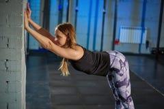 Menina muscular bonita nas caneleiras cinzentas que fazem o esticão Ostenta o gym no estilo industrial Imagens de Stock Royalty Free