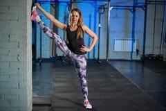 Menina muscular bonita nas caneleiras cinzentas que fazem o esticão Ostenta o gym no estilo industrial Foto de Stock