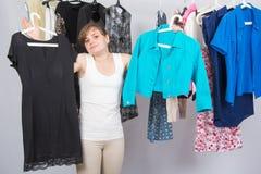 A menina não conheceu o que escolher da roupa no vestuário foto de stock