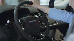 Menina não reconhecida no compartimento de passageiro do carro novo A mulher bem sucedida examina o automóvel novo Concessionário vídeos de arquivo