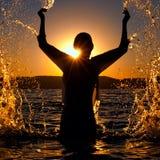 Menina na água no por do sol Fotos de Stock Royalty Free