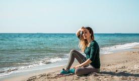 Menina na aptidão do sportswear pelo mar que escuta imagem de stock