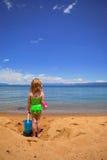 Menina na areia no lago Fotos de Stock Royalty Free