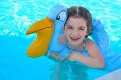 Menina feliz com o brinquedo inflável do anel na água imagem de stock royalty free