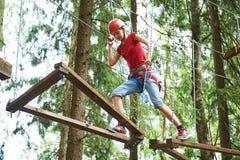 Menina na atividade de escalada no fio alto Forest Park Imagem de Stock
