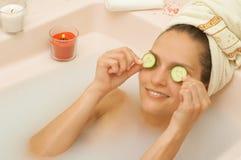 A menina na banheira aplica fatias do pepino à cara Fotografia de Stock