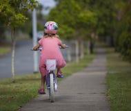 Menina na bicicleta afastado Foto de Stock Royalty Free