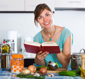 Menina na caçarola e nos vegetais da cozinha imagem de stock