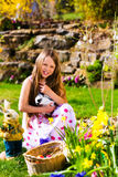 Menina na caça do ovo da páscoa com coelhinho da Páscoa vivo Fotos de Stock