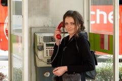 A menina na cabine de telefone velha fotografia de stock