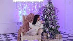 Menina na cadeira com champanhe perto da árvore de Natal filme