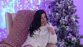 Menina na cadeira com champanhe perto da árvore de Natal video estoque