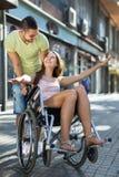 Menina na cadeira de rodas com o amigo exterior Fotos de Stock Royalty Free