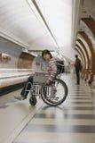 Menina na cadeira de rodas no metro Foto de Stock Royalty Free