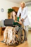 Menina na cadeira de rodas que trabalha no portátil Imagens de Stock Royalty Free
