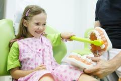 Menina na cadeira dos dentistas que toothbrushing um modelo fotografia de stock royalty free