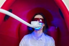 Menina na cadeira no procedimento do alvejante dos dentes fotografia de stock