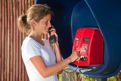 Menina na caixa de telefone ao ar livre Fotografia de Stock