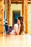 Menina na calças da sarja de Nimes que encontra-se no assoalho Fotos de Stock Royalty Free
