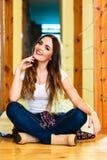 Menina na calças da sarja de Nimes que senta-se no assoalho Imagens de Stock