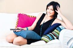 Menina na cama com controlador remoto à disposicão Imagem de Stock Royalty Free