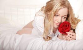 Menina na cama com Rosa Fotografia de Stock Royalty Free