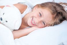 Menina na cama com urso de peluche Fotos de Stock Royalty Free