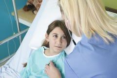 Menina na cama de hospital com a enfermeira foto de stock